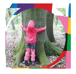 Kind umarmt Baum